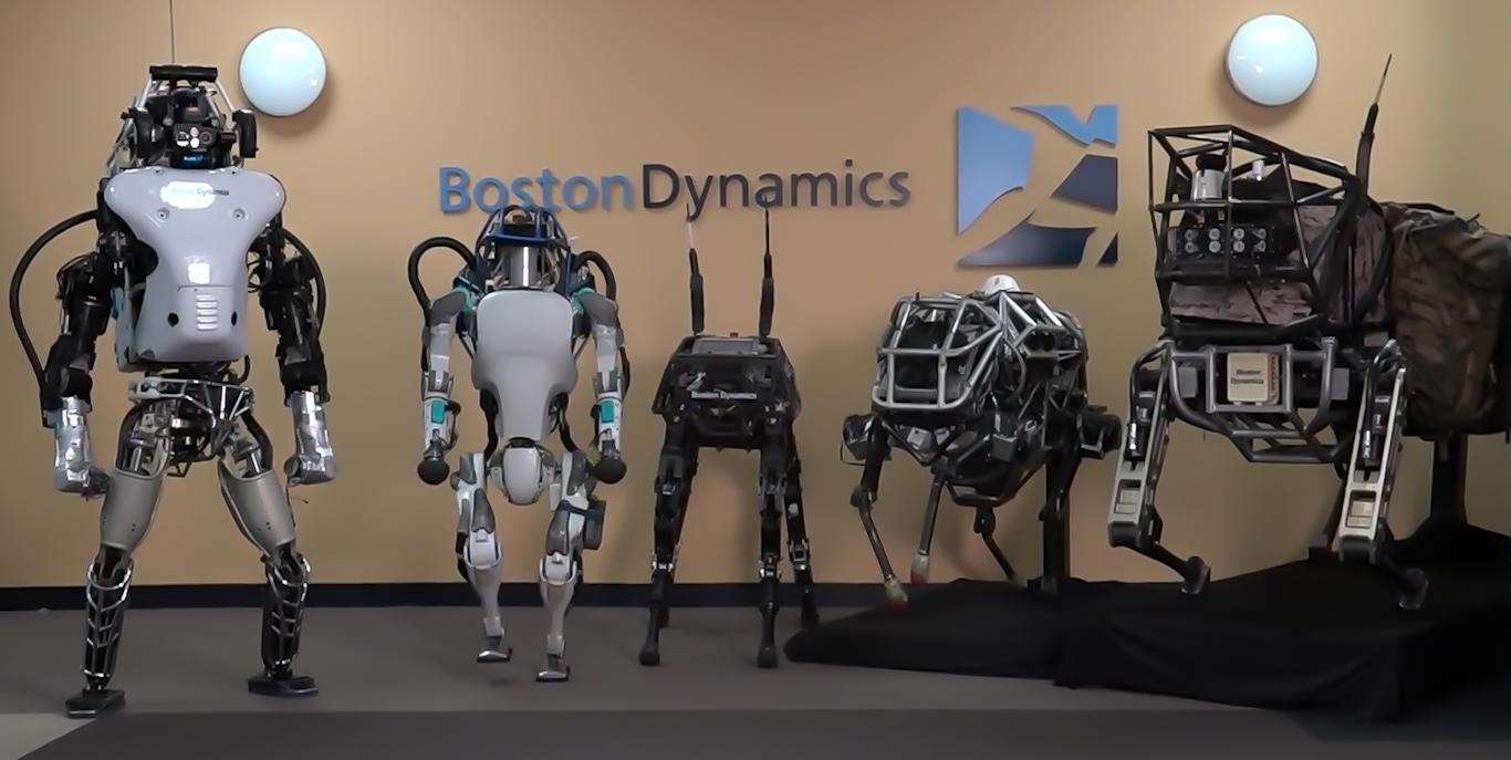 Atlas (druhý zleva) a další roboti, se kterými Boston Dynamics pracuje