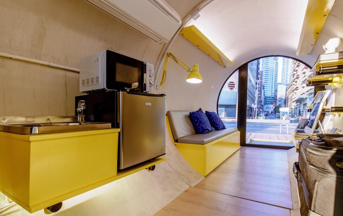 Pohled na jednoduché kuchyňské zařízení a pohovku, která se dá rozložit na postel.