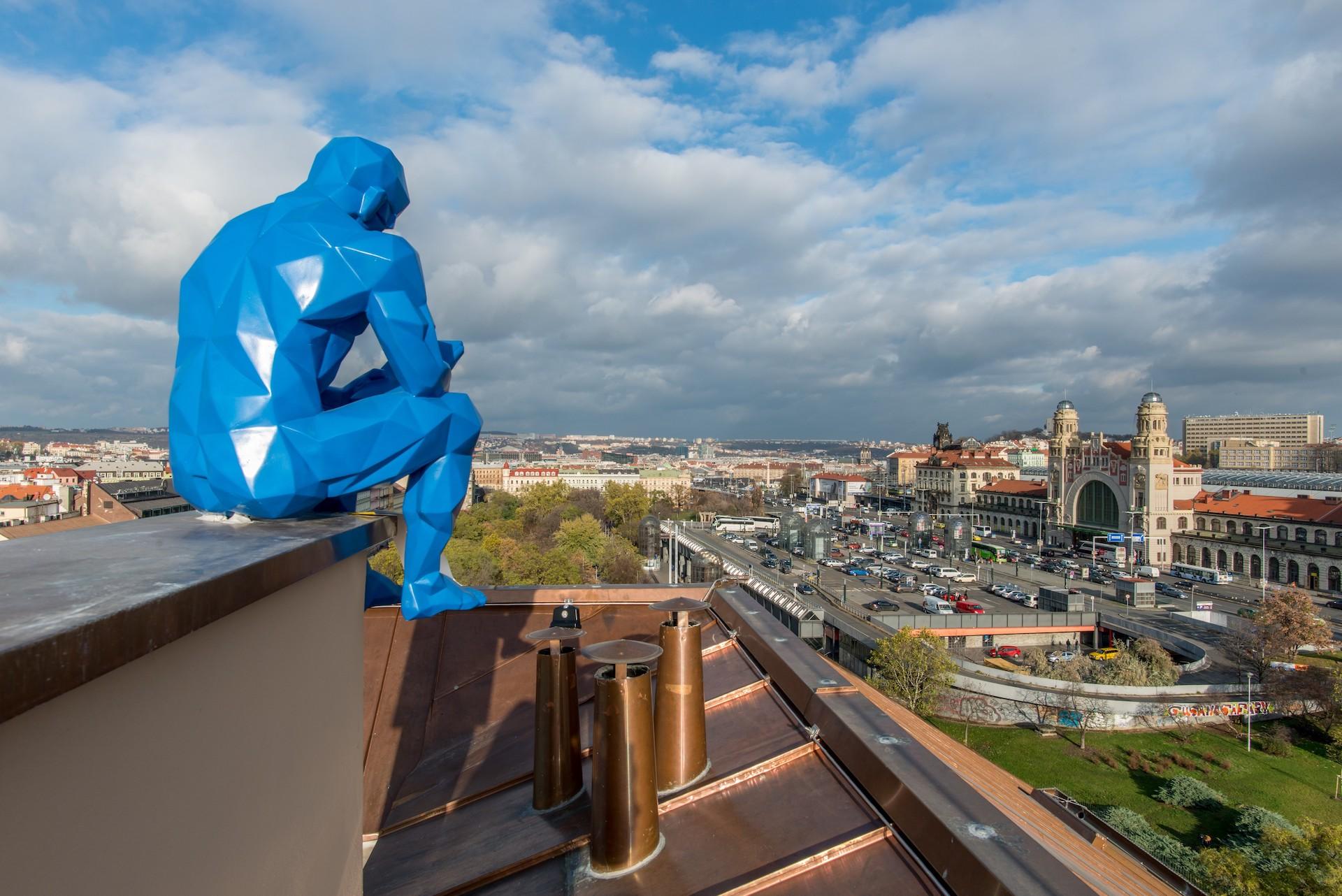 Blueman sedí i na střeše s výhledem na Hlavní nádraží