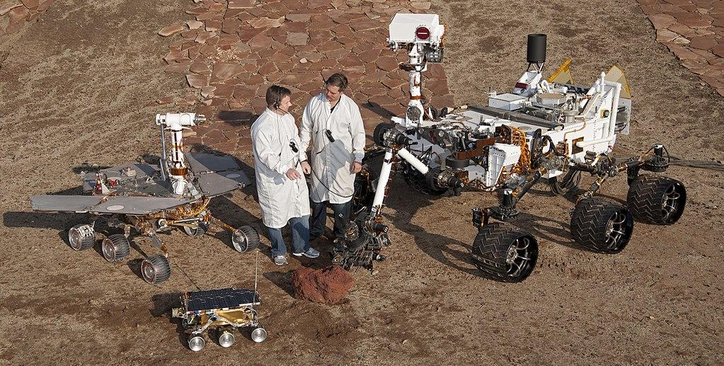 Rovery od NASA, v modelech 1:1. Vpředu Sojourner (1997), vlevo Opportunity (2004), vpravo Curiosity (2012)