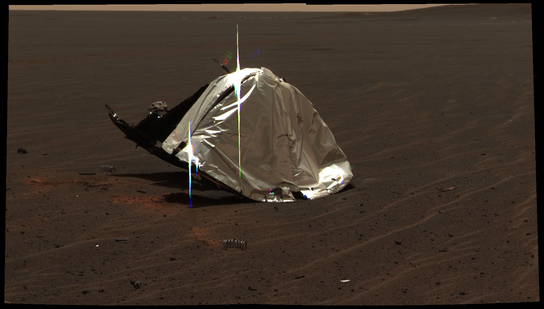 Tepelný štít roveru Opportunity. Za ním vlevo lze vidět první meteorit nalezený mimo Zemi