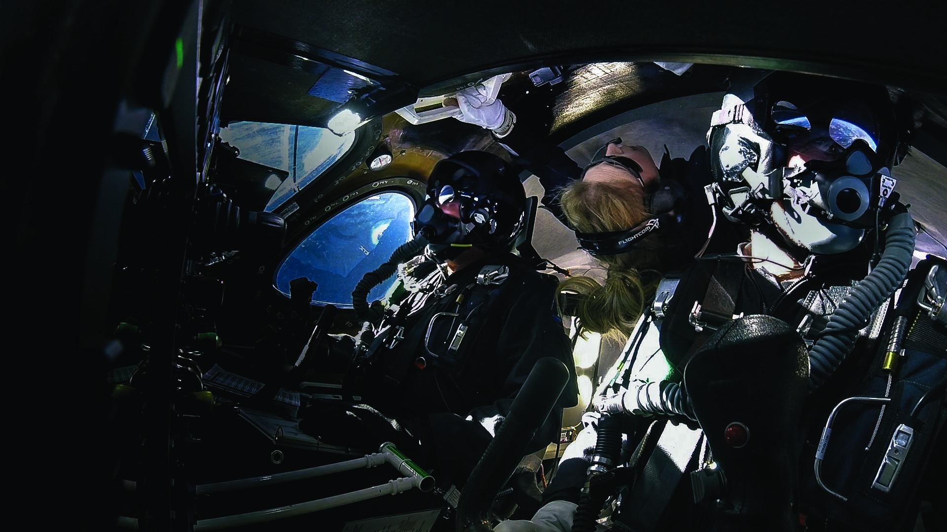 Piloti Dave Mackay a Michael Masucci a trenérka astronautů Beth Moses v kokpitu VSS Unity